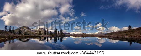 Panoramic view of the snow-capped mountains reflected on the lake, playful clouds  - stock photo