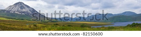 Panoramic view of the white quartzite peak of Mount Errigal rising above a peat bog beside Lough Nacung, Donegal, Ireland, with the mountain range of Derryveagh National Park in the background. - stock photo