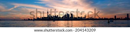 Panoramic view of Toronto city skyline over ontario lake at sunset - stock photo