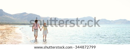 Panoramic view of tourist couple on holiday walking along the sea shore holding hands on vacation, sky with sun light, outdoors space. Romance and dynamic honeymoon calm lifestyle, summer exterior.