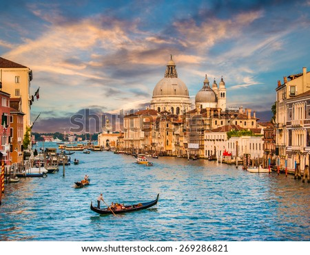 Panoramic view of traditional Gondola on famous Canal Grande with Basilica di Santa Maria della Salute in beautiful golden evening light at sunset in Venice, Italy - stock photo