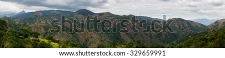 Panoramic view of tropical mountain range wih cloudy sky