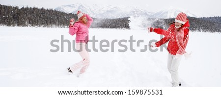 Panoramic view of two joyful and energetic friends playing games and having fun, having a snow ball fight in the snow mountains landscape during a skiing holiday on a sunny winter day. - stock photo