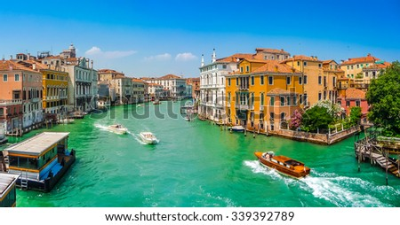 Panoramic view of typical Canal Grande scene with colorful houses and busy boats and gondolas on a  sunny day in Venice, Italy - stock photo