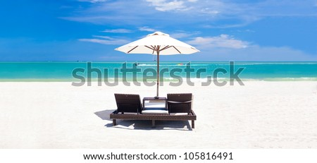 panoramic view of umbrella and two chairs on a tropical beach - stock photo