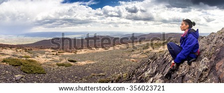 Panoramic view of woman hiker on a rocky mountain. Spring hike through the hills of southern Urals. - stock photo
