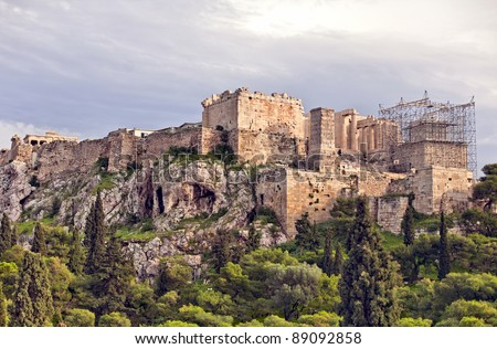 Panoramic view on Acropolis hill surrounded by green trees in Athens, Greece