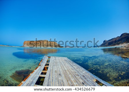 panoramic view on Balos beach, Crete, Greece. in the foreground an old bridge in the background a small lonely island. calm smooth sea water without waves - stock photo