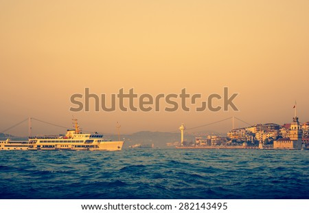 Panoramic view on Fatih Sultan Mehmet Bridge and steamboats - Bosporus bridge at sunset. Cityscape view of Istanbul with a passenger ships, Maiden's Tower and lighthouse in Bosporus. - stock photo