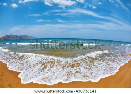 panoramic view on sunny beach with yellow sand and blue sea, Crete, Greece - stock photo