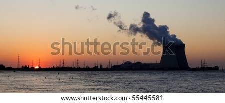 Panoramic view on the nuclear power plant in Doel, Antwerp, Belgium, with the sun going down behind the electricity towers leading to a beautiful industrial scenery - stock photo