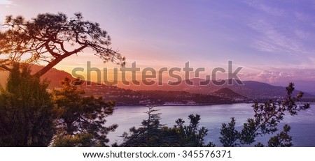 Panoramic view over a coastal town in France, French Riviera, hills and a bay at sunset - stock photo