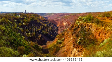 Panoramic view to extended colorful open-pit mine with drawn hills in the foreground - stock photo