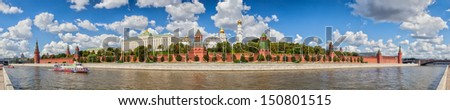Panoramic view to Moscow Kremlin from Sofiyskaya embankment over river with ship under clouds, Russia
