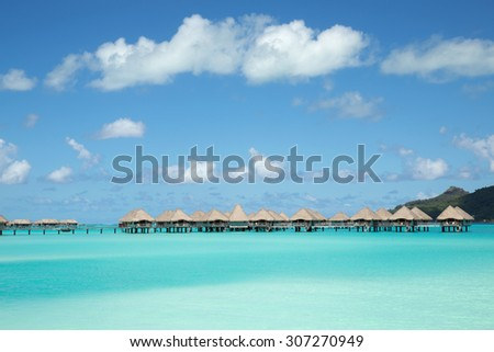 panoramic view to paradise turquoise lagoon with chain of over-water bungalows and blue sky, Bora Bora island, near Tahiti, French Polynesia, Pacific ocean - stock photo