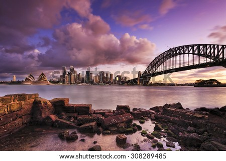 panoramic view to Sydney CBD, Harbour bridge, Harbour and other landmarks from across the Harbour at low tide at sunset - stock photo