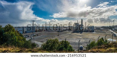 Panoramic view to the oil-processing plant in Øygarden region in Norway near Bergen, with cumulus clouds in the sky