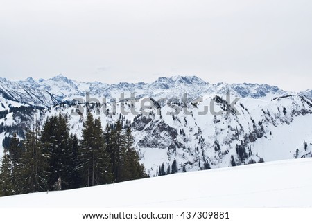 Panoramic vista of snow covered mountains and valleys stretching away into the distance viewed from a snowy summit on a cold bleak winter day - stock photo