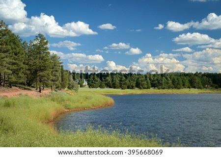 Panoramic, wide angle shot of tranquil Fool Hollow Lake, Arizona, USA with beautiful clouds in desert blue sky and lush green nature. - stock photo