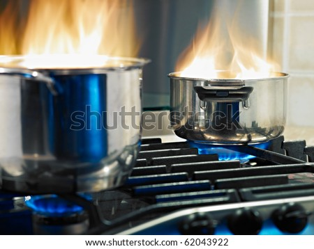 pans in fire on stoves. Horizontal shape - stock photo