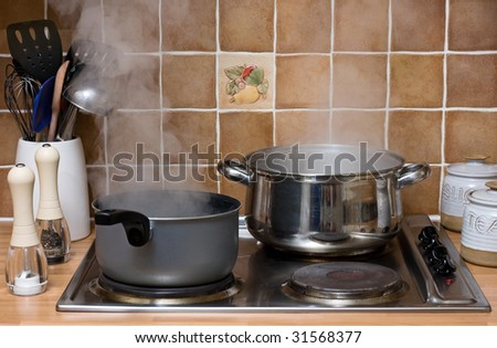 Pans of water boiling on an electric hob in a kitchen - stock photo