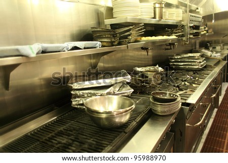 Pans on the stove in a restaurant kitchen.