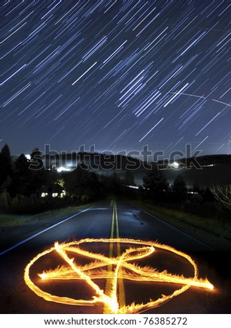 Pantagram made of fire in the middle of a country rural road at night time with a long exposure of star trails in the sky - stock photo