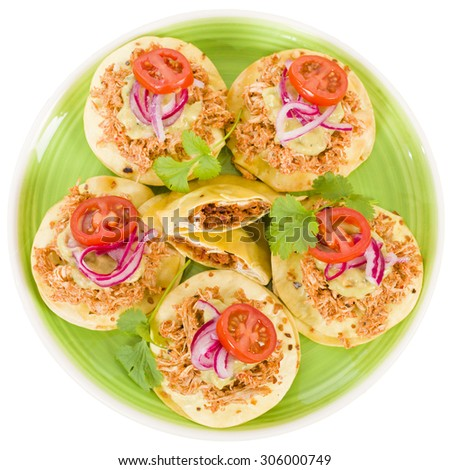 Panuchos - Mexican corn tortillas filled with refried beans and topped with shredded chicken, guacamole, pickled red onions and tomato. Isolated on white. - stock photo