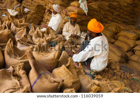 PAONTA SAHIB, INDIA - MAY 23: Unidentified Sikh men pack sacks full of charity grain in part of their philanthropic religious duties to help the needy on May 23, 2009 in Paonta Sahib, India - stock photo