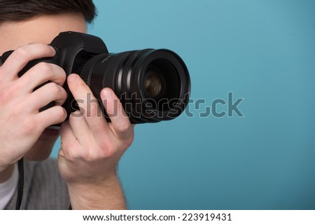 Paparazzi man taking picture with photo camera. Male photographer taking photos with digital camera  - stock photo