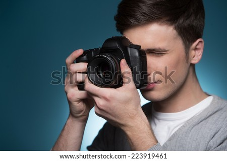 Paparazzi man taking picture with photo camera. side view of photographer taking photos on blue background - stock photo
