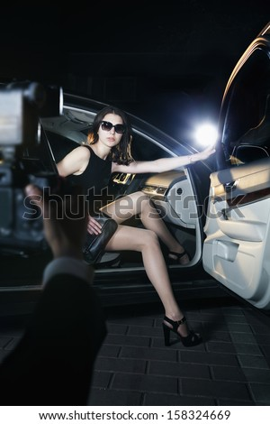 Paparazzi photographer taking photo of young beautiful woman stepping out of car  - stock photo