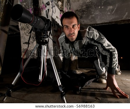 paparazzi  photographer with a camera mounted on tripod - stock photo