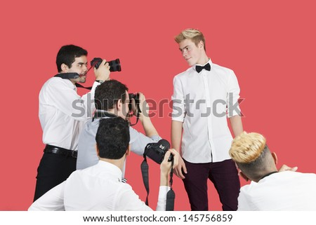 Paparazzi taking photographs of male actor over red background - stock photo