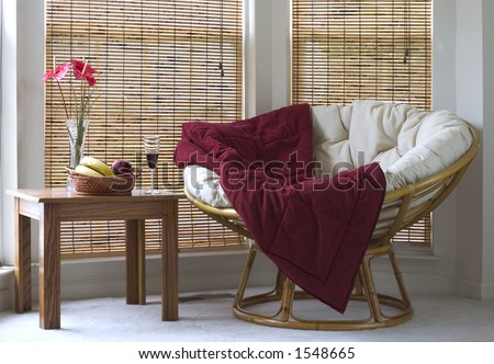 papasan chair near coffee table with wine and fruits - stock photo