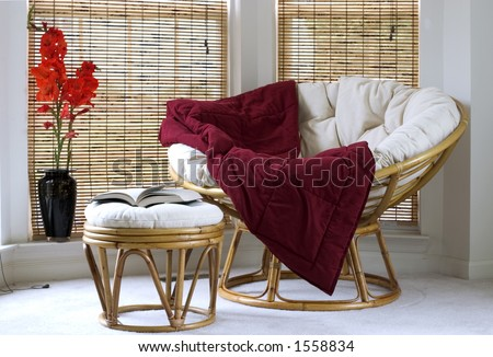 Papasan chair w cushion stool and vase with Gladiolus flowers - stock photo