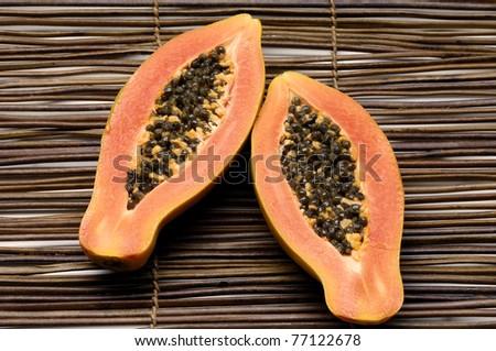 Papaya fruit sliced on half isolated on mat - stock photo