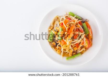 papaya salad on dish with white paper background - stock photo