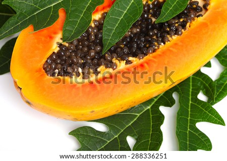 papaya with seeds and green leaf isolated on a white background - stock photo