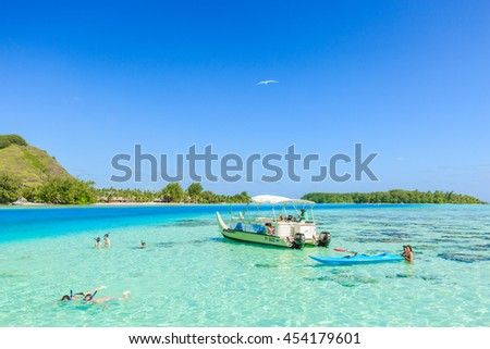 PAPEETE, FRENCH POLYNESIA - JULY 16, 2016 : The Tourists swimming and feeding sharks and Stingrays in beautiful sea at Moorae Island, Tahiti PAPEETE, FRENCH POLYNESIA on July 16, 2016