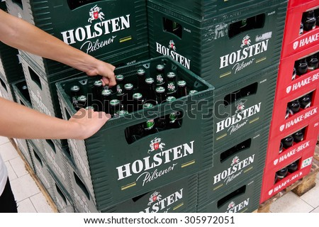 PAPENBURG, GERMANY - AUGUST 11: Stack of Holsten pilsener beer crates in a Kaufland hypermarket. Holsten Brewery is owned by the Danish company Carlsberg Group. Taken in Germany on August 11, 2015 - stock photo