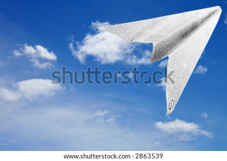 Paper aeroplane made of newspaper page in flight - stock photo