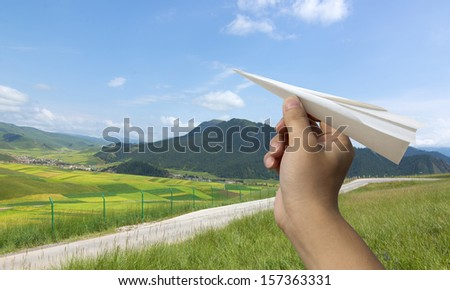 Paper airplane blue grass - stock photo
