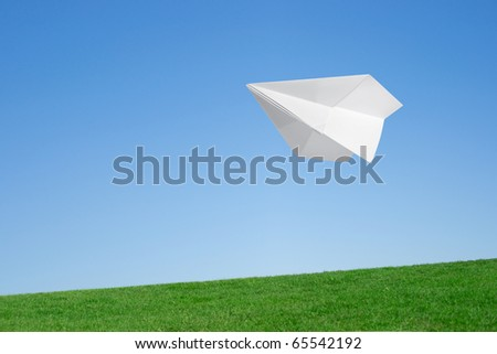 Paper airplane flying over the lawn against the blue sky - stock photo