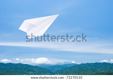 Paper airplane flying upon the mountain toward sky - stock photo