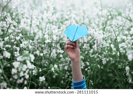 Paper airplane in children hands on white background - stock photo