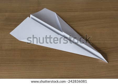 Paper Airplane in claccic arrow shape on a wooden table - stock photo