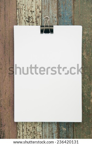 Paper and clip on vintage wood for background and text - stock photo