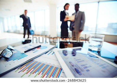 Paper and electronic business documents on desk - stock photo