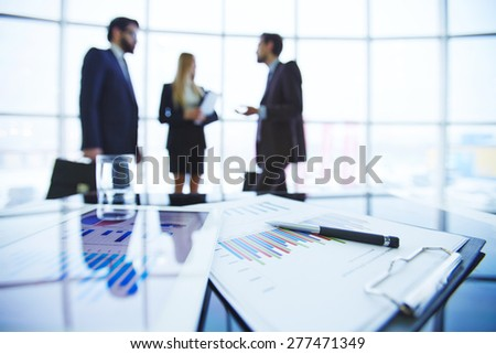 Paper and electronic financial documents at workplace on background of business group